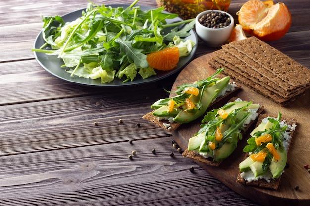 Vollkorn-knäckebrot mit käse, rucola, mandarine und frischem grünem salat