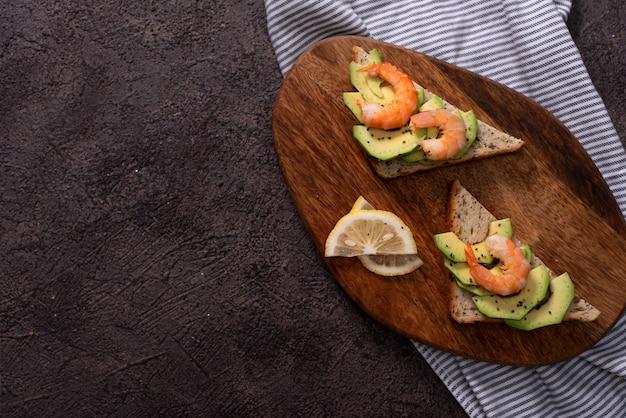 Vollkorn-toastbrotscheiben mit guacamole, gebratenen garnelen und gebratenen speckstücken auf holzbrett selective focus, fokus auf die vorderseite der garnelen beim ersten brot