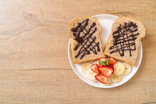 Vollkornbrot mit frischer banane, erdbeere und schokolade zum frühstück geröstet