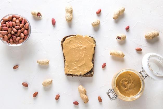 Vollkornbrot mit walnusspaste mit erdnüssen. essen vegan. flach liegen. von oben betrachten.