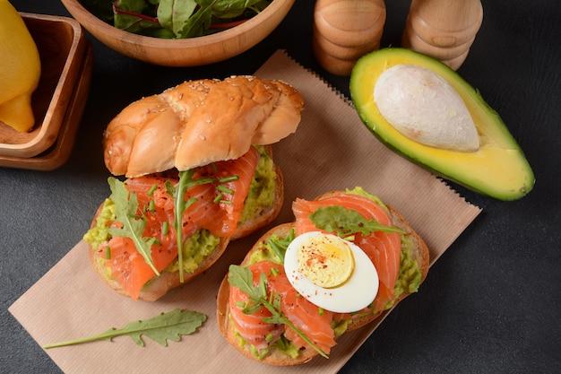 Vollkornbrot-sandwich mit avocadopaste und lachs, ei und rucolablättern