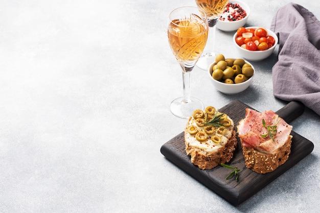Vollkornbrotsandwiche mit frischkäse, speck und oliven auf einem hölzernen schneidebrett. ein glas weisswein.