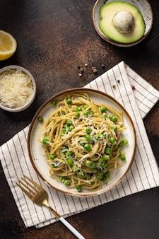 Vollkornnudel-spaghetti mit erbsen und avocado