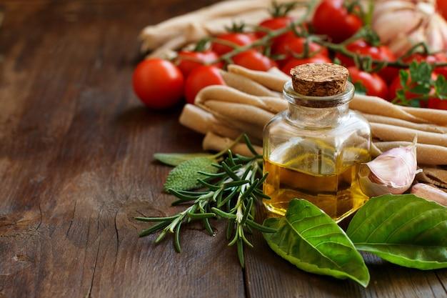 Vollkornnudeln, gemüse, kräuter und olivenöl auf holztisch