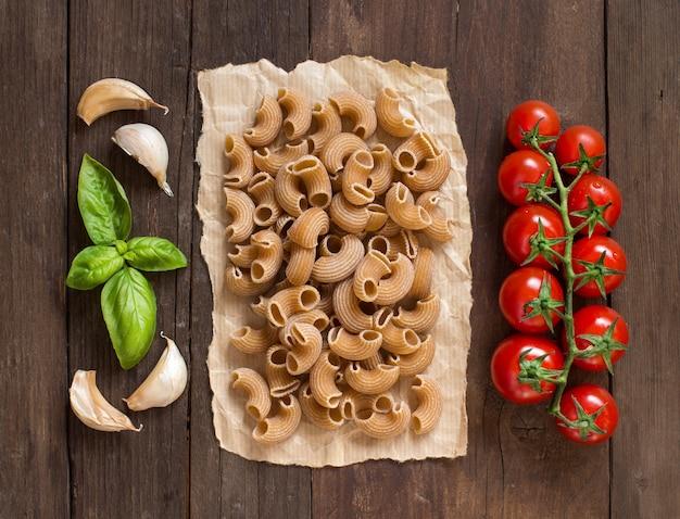 Vollkornnudeln mit knoblauch, tomaten und basilikum auf holztisch