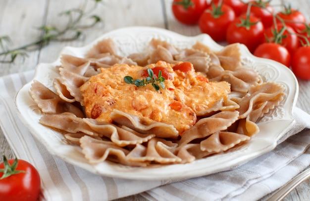 Vollkornnudeln mit stracchino-käse und frischen tomaten hautnah