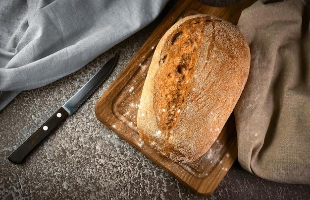 Vollkornroggenbrot auf einem schneidebrett mit messer auf grauer oberfläche