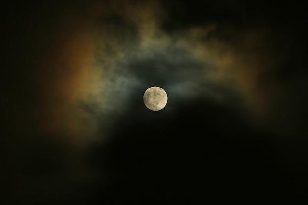 Vollmond auf dem dunklen himmel mit dem mondschein, der über die wolken nachdenkt.