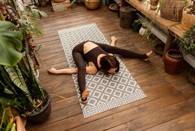 Vollschuss frau, die auf yogamatte streckt