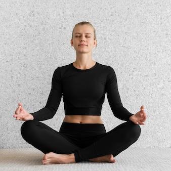 Vollschuss frau, die drinnen meditiert