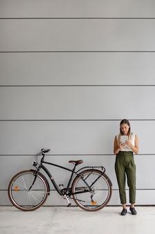 Vollschuss frau, die nahe fahrrad steht