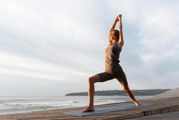 Vollschuss frau, die yoga auf matte nahe meer praktiziert
