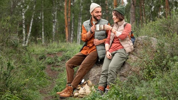 Vollschuss glückliches paar, das heißes getränk in der natur genießt