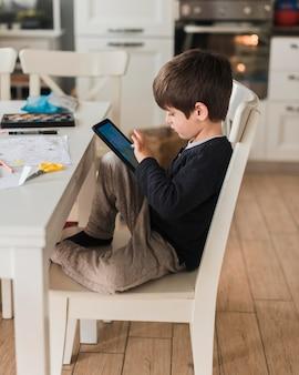 Vollschusskind auf stuhl mit tablette