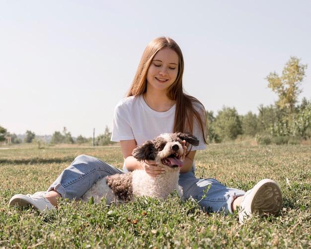Vollschussmädchen, das auf gras mit hund sitzt