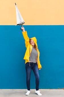 Vollschussmädchen, das gelben regenmantel trägt