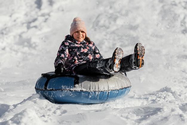 Vollschussmädchen, das im schnee spielt