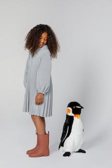 Vollschussmädchen, das mit pinguin aufwirft
