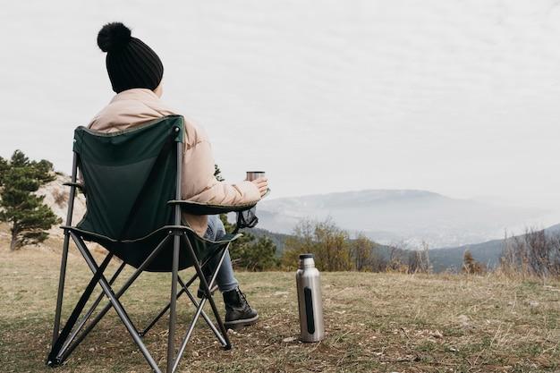 Vollschussmann, der draußen auf stuhl sitzt