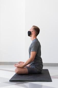 Vollschussmann mit maske, die yoga-pose übt
