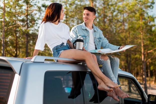 Vollschusspaar sitzt auf auto mit karte