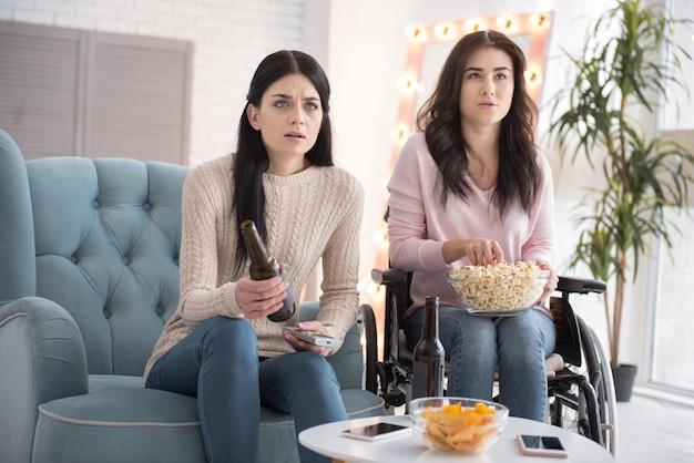 Vollständiges eintauchen. unbehagliche schwester und behinderte frau in bezug auf film und popcorn mit getränk essen Premium Fotos