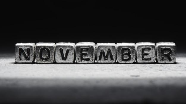 Volumetrische inschrift november silberne metallwürfel auf einem dunklen schwarzen hintergrund. terminkalender, persönliche planung und zeitmanagement