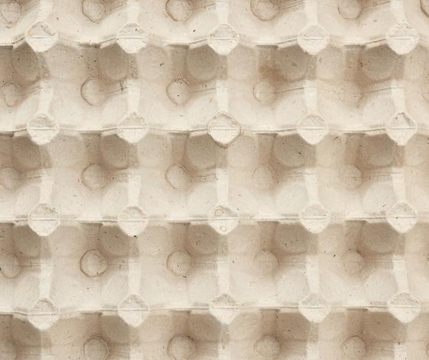 Volumetrische textur einer beigen papier-eierablage