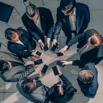 Von der draufsicht. business-team verwendet ihre smartphones, um mit finanzdaten zu arbeiten.