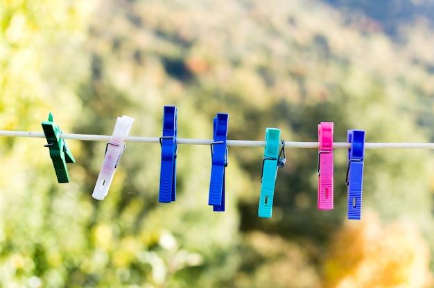 Von der wäscheleine hängende wäscheklammern in verschiedenen farben mit unscharfem hintergrund.