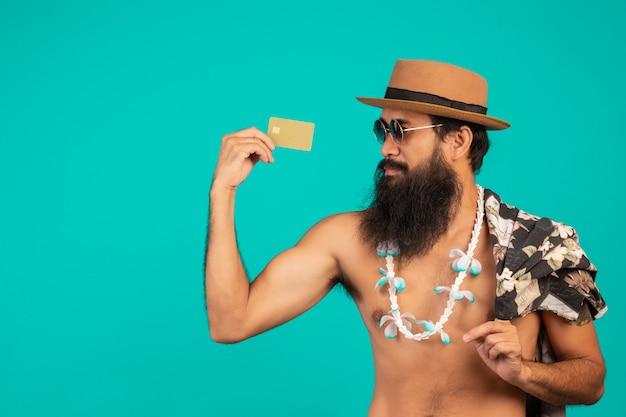 Von einem glücklichen langen bartmann, der einen hut, ein gestreiftes hemd tragend trägt und halten eine goldene kreditkarte auf einem blau.