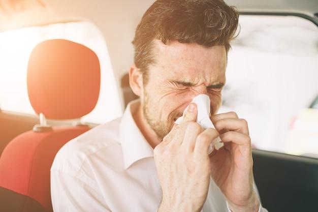 Von einem jungen mann mit taschentuch. kranker kerl hat laufende nase. mann macht eine heilung für die erkältung im auto.