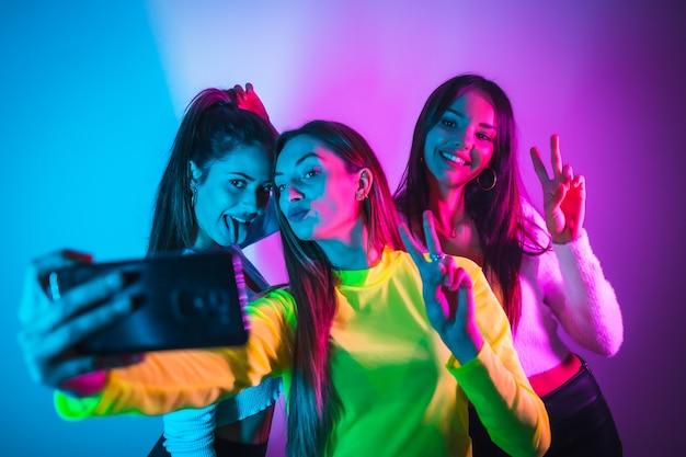 Von freunden, die in einer disco mit blauen und rosa neonlichtern feiern und spaß daran haben, ein foto zu machen