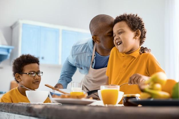 Von gefühlen überwältigt. liebevoller junger vater, der seinen kleinen sohn auf die wange küsst, während er in der küche frühstückt