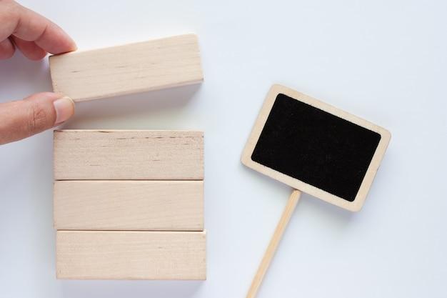 Von hand pflücken das hölzerne spielzeug mit tafelaufkleber