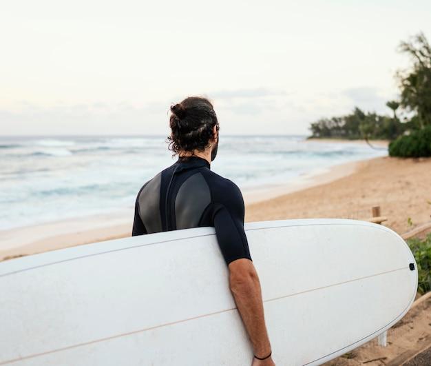 Von hinten schuss surfer mann im freien