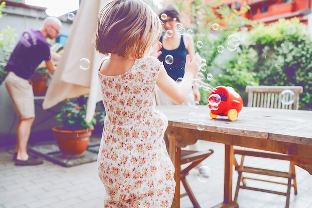 Von hinten weibliches kind, das mit luftblasenseife spielt