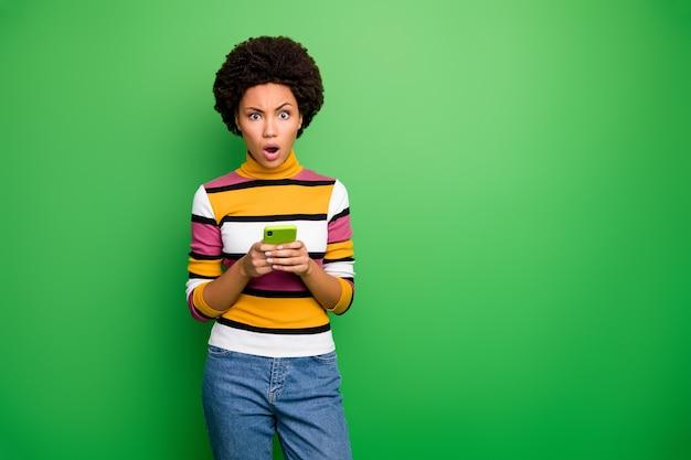 Von hübscher dunkler haut lockige dame, die telefonhände hält, die schreckliche falsche nachrichten lesen unglaubliches episches versagen tragen lässige gestreifte pulloverjeans