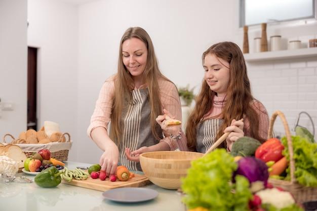 Von ihrer mutter lernt ein junges mädchen, wie man ein abendessen zubereitet. gesunde mahlzeiten zubereiten. in der küche eine glückliche familie. das gemüse und das obst werden von der mutter und ihrer tochter zubereitet.