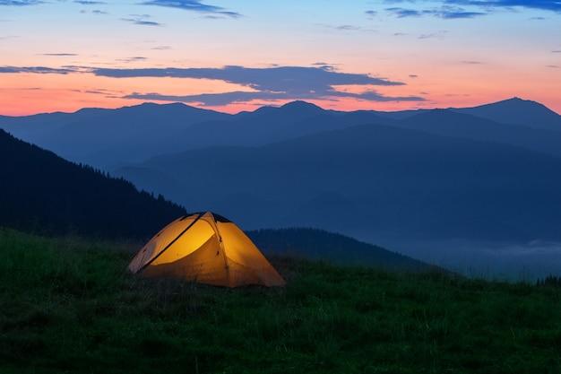 Von innen beleuchtetes orangefarbenes touristenzelt auf dem berg. am frühen morgen oder sonnenuntergang.