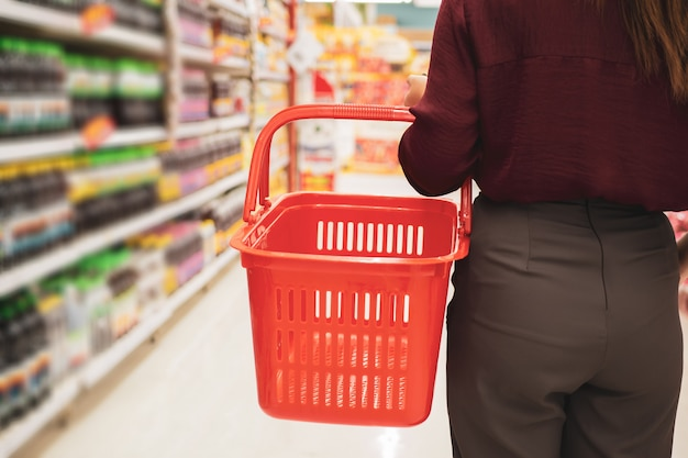 Von junger frau mit korb im supermarkt geerntet