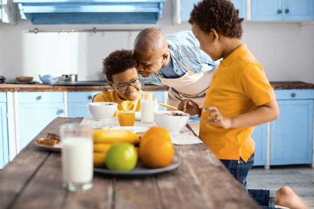 Von liebe überwältigt. sanfter junger vater, der mit seinem kleinen sohn liebevoll ist, während er in der küche frühstückt