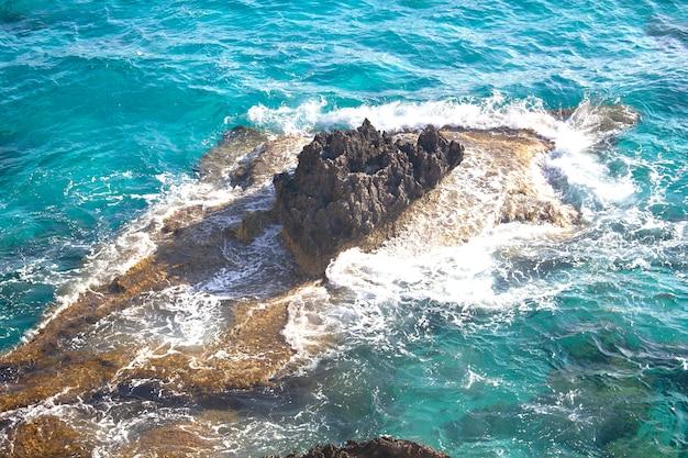 Von meereswellen gewaschene felsen. türkisklares wasser, urlaub, meereslandschaft