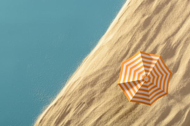 Von oben aufnahme der blauen oberfläche mit strukturiertem sandstrand und bunt gestreiftem regenschirm oben.