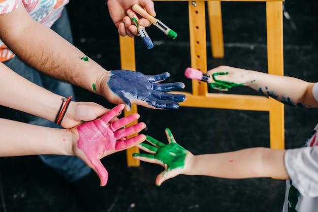 Von oben betrachten. hände mit farbigen farben verschmiert. zeichne mit der ganzen familie