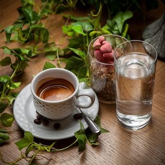 Von oben espressokaffee mit wasser und traubenzweig und kaffeebohnen in der tasse