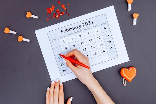 Von oben frau kreist datum auf kalender des jahres 2021 während valentinstag 14. februar.