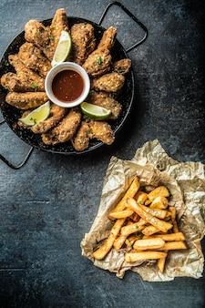 Von oben gebratene chicken wings chilisauce limette und pommes frites.