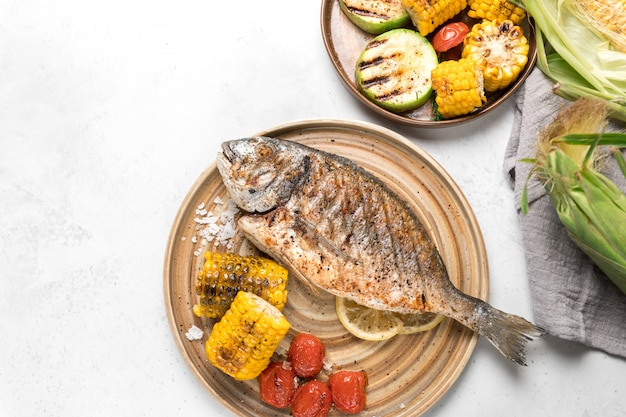Von oben gegrillter fisch mit zitrone, serviert mit verschiedenen gemüsesorten auf gerichten