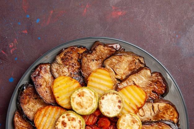 Von oben gesehen gebackene gemüsekartoffeln und auberginen frisch aus dem ofen im dunkeln